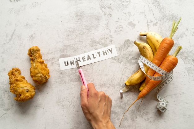 Person's hand cutting unhealthy word near fried chicken with banana and carrots rolled in measuring tape