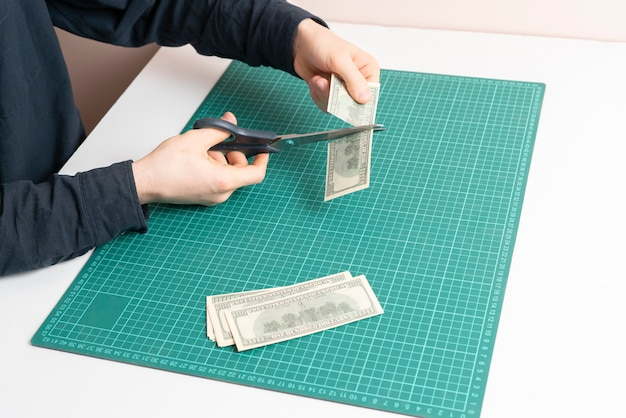 A person's hand cutting a us hundred dollar cash banknote as a symbol of bunkrupt and busines problems