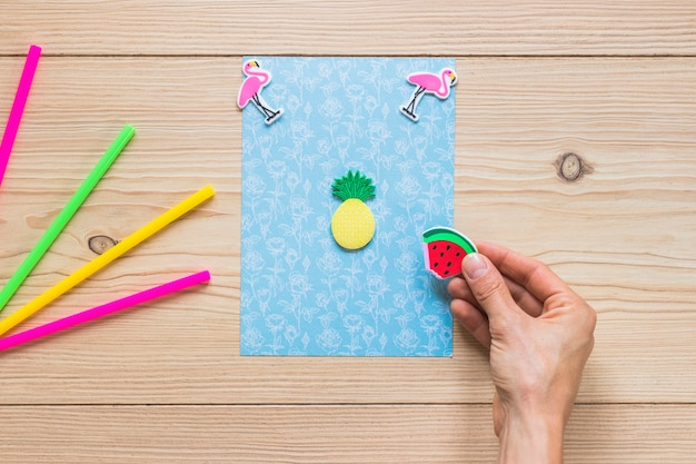 La mano di una persona che decora la carta blu con l'autoadesivo su fondo di legno