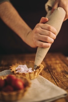 A person's hand filling the tart with pink whipped cream from icing bag on wooden table