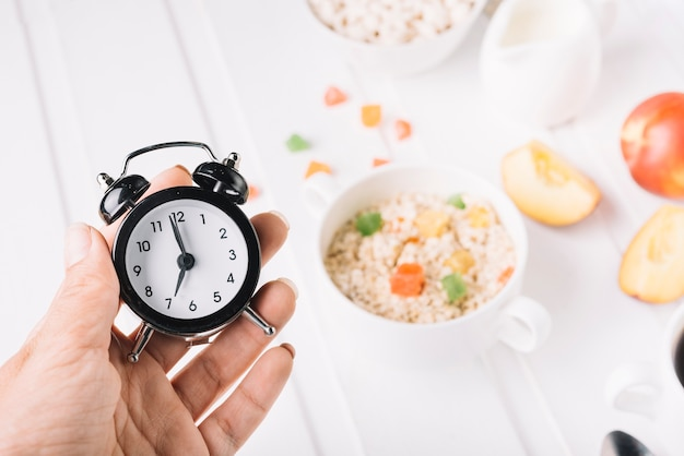 A person's hand holding alarm clock in hand over the breakfast on the table