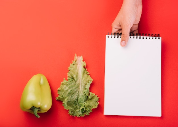 Person's hand holding blank spiral notepad near lettuce and green bell pepper over red surface