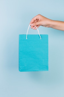 A person's hand holding blue paper shopping bag