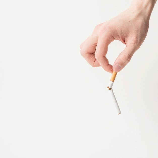 Person's hand holding broken cigarette on white background