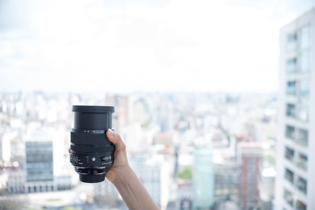 Person's hand holding camera lens in front of blurred buildings background
