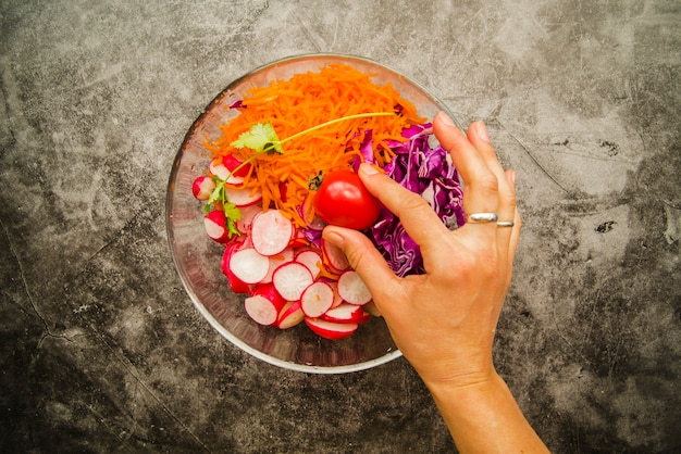 Person's hand holding cherry tomato in fresh salad in bowl
