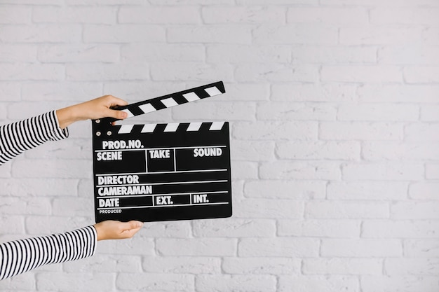 A person's hand holding clapperboard in front of brick wall