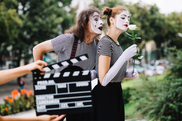 A person's hand holding clapperboard in front of mime couple