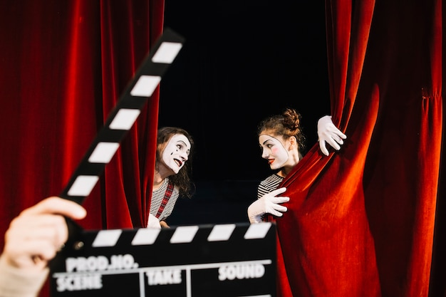 A person's hand holding clapperboard in front of two mime artist performing behind red curtain