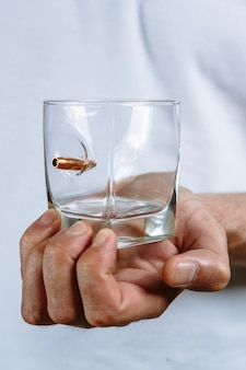 A person's hand holding a clear glass with a bullet stuck in it