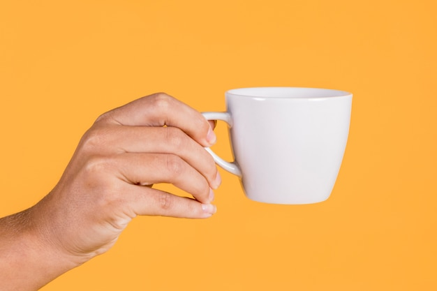 Person's hand holding coffee cup against colored background