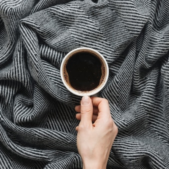 Person's hand holding coffee cup over cloth