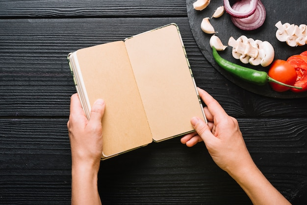 A person's hand holding diary near sliced vegetables on black wooden surface