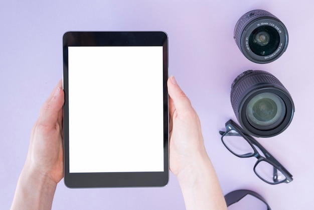 Person's hand holding digital tablet over camera lens and spectacles on lavender background