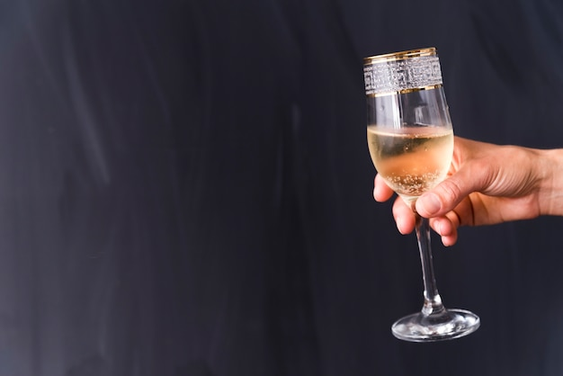 A person's hand holding elegant champagne glass with bubble against black background