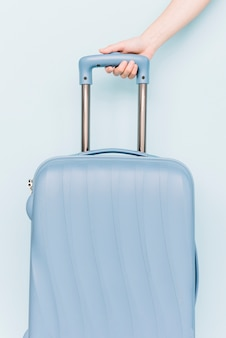A person's hand holding handle of travel baggage against blue backdrop