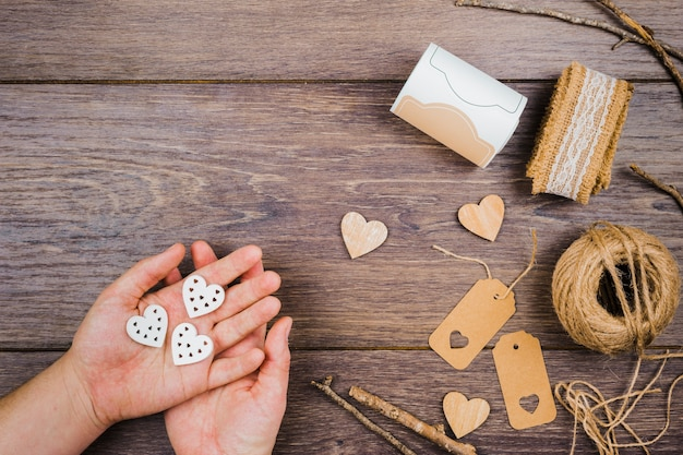 A person's hand holding heart shape with jute spool; tags; sticks and lace on wooden desk