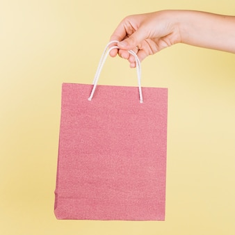 A person's hand holding pink paper shopping bag on yellow background