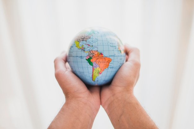 A person's hand holding small globe