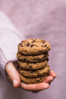 A person's hand holding stack of chocolate chip cookies