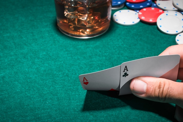 A person's hand holding two aces heart shape and club card on poker table
