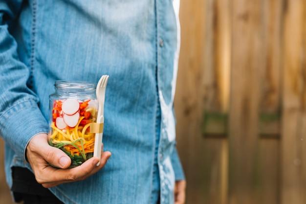 A person's hand holding vegan pasta salad in mason jar