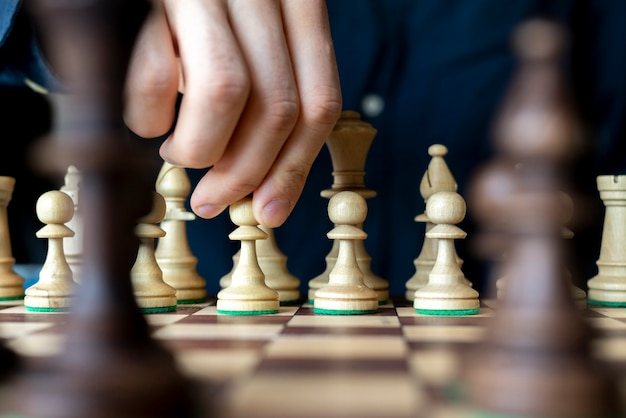 A person's hand making a move in a chess game, thinking on a strategy