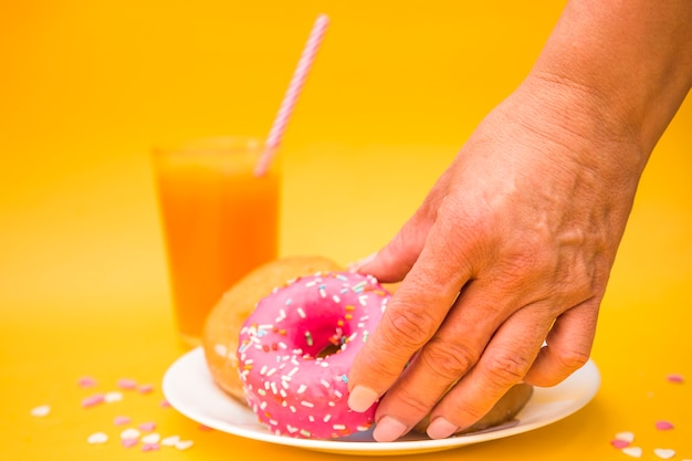 A person's hand picking up pink donut