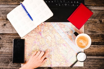Person's hand pointing at location on map with coffee and smartphone on table
