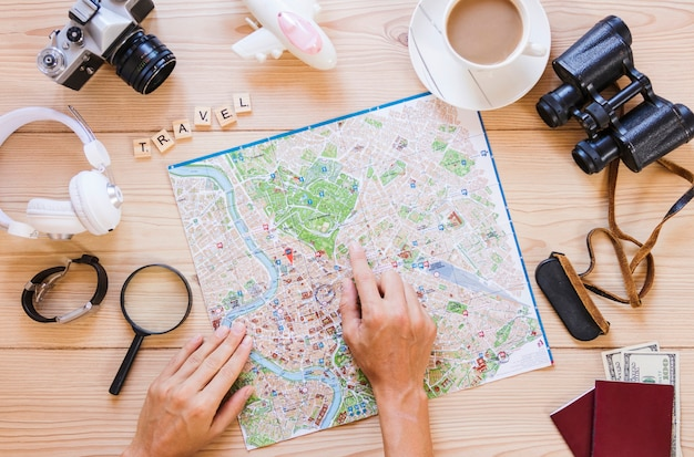 Person's hand pointing at location on map with cup of tea and traveler accessories on wooden surface