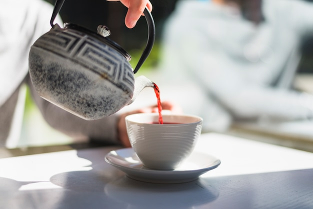 A person's hand pouring red tea in the white ceramic cup on the white table in the sunlight