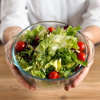 Person's hand showing green leafy vegetable salad with red cherry tomatoes