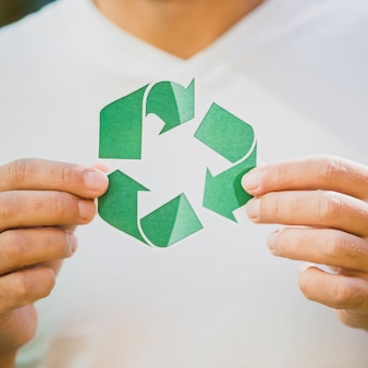 A person's hand showing recycle icon
