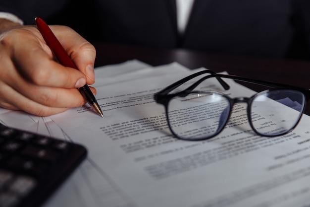 デスクで人の手で書類に署名します。ビジネスコンセプト。