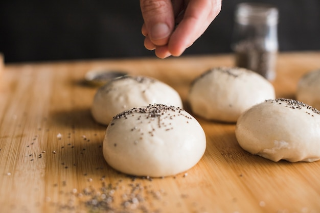 A person's hand sprinkling chia seeds over the ball of buns on wooden backdrop