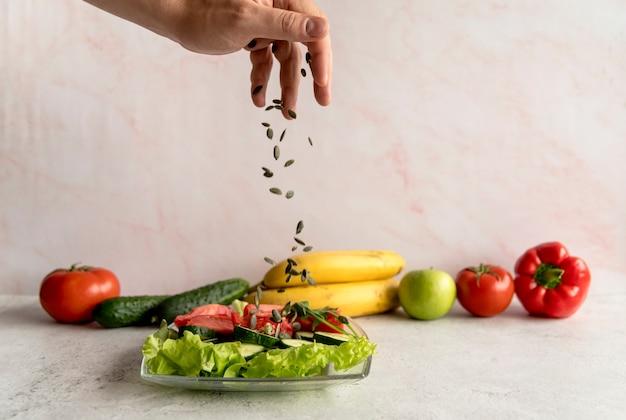 Person's hand sprinkling pumpkin seeds over vegetable salad