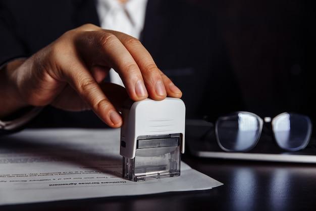 Штемпель руки человека с утвержденным штампом на документе на столе. бизнес-концепция