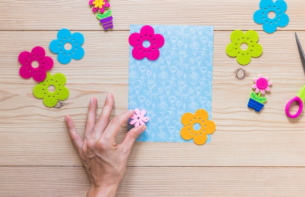 A person's hand sticking flower patch on scrapbook card