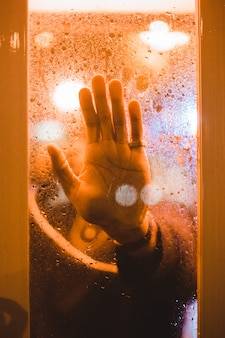 Рука человека касается прозрачного стекла