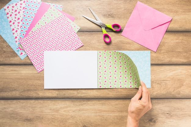 A person's hand turning scrapbook paper over the table