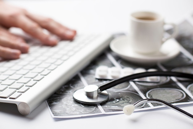 Person's hand typing on keyboard near ultrasound scan report; blister of pills and coffee cup on desk