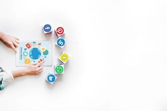 ソーシャルメディアアプリケーションのブロックでデジタルタブレットを使用する人の手