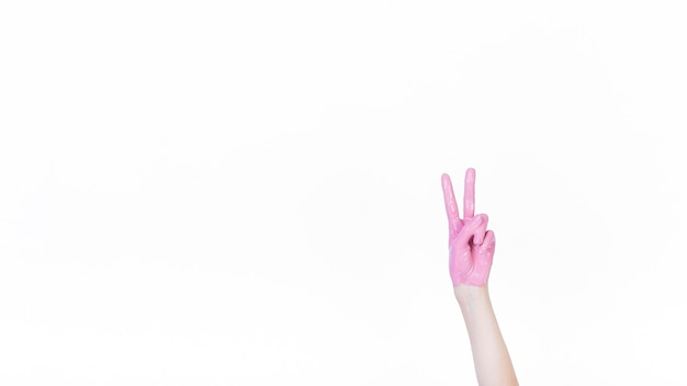 A person's hand with pink paint showing peace sign