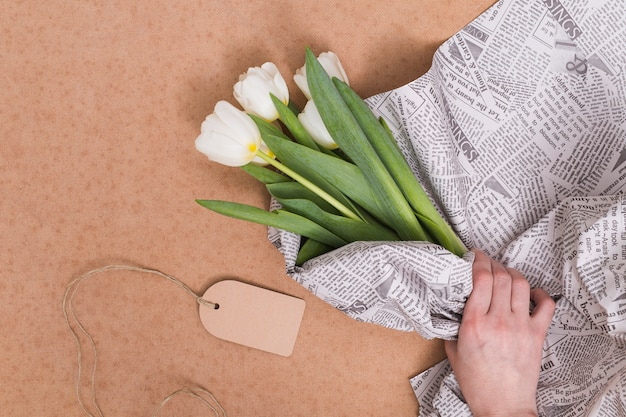 Person's hand wrapping white tulip flowers in newspaper with price tag over brown background