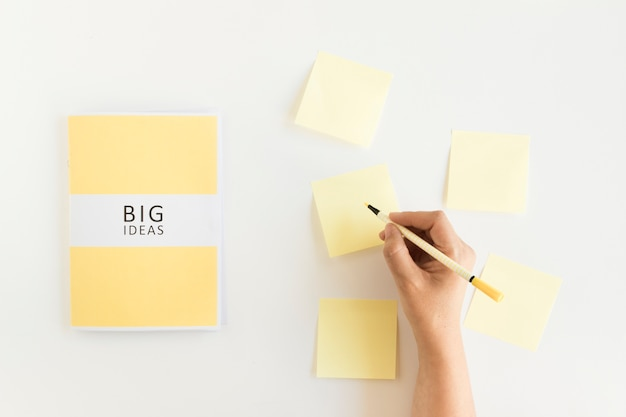 A person's hand writing on adhesive notes near big ideas diary