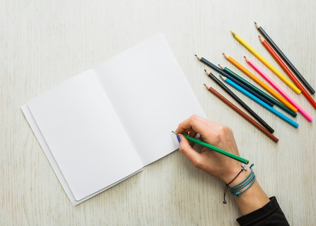 Person's hand writing on blank white book using color pencil