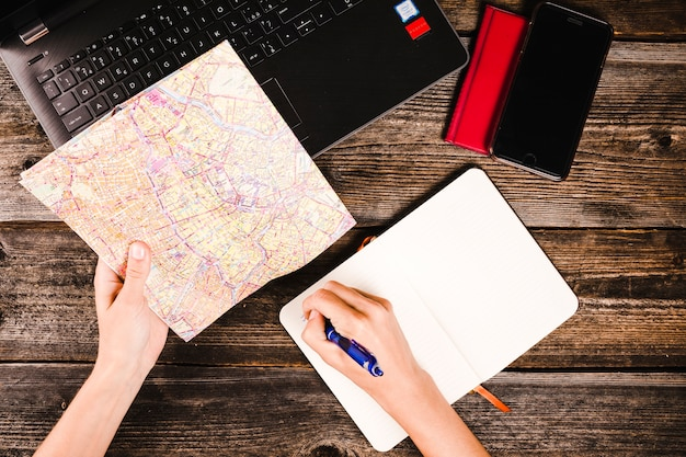 A person's hand writing in notepad while holding map over table