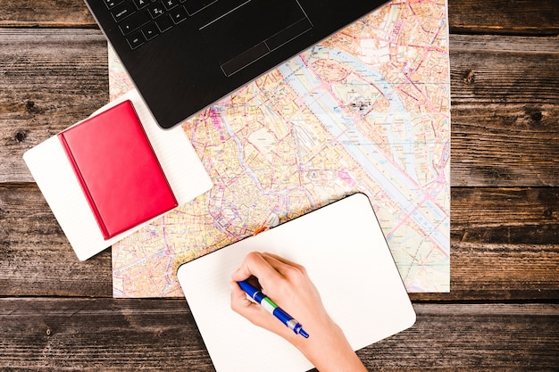 Person's hand writing on notepad with diary and map on wooden table