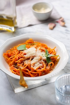 A person's hands are sprinkled with parmesan cheese pasta in tomato sauce in a geometric-shaped plate with a fork. in the background, a bottle of olive oil and garlic