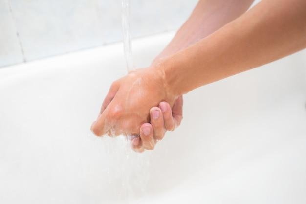 浴室で水を注いで洗う人の手